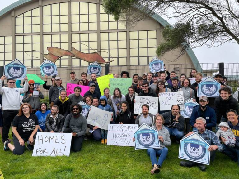 """YIMBYs of all ages posing for a group photo, holding signs that say """"support working families"""", """"homes for all"""", and """"affordable housing now"""""""